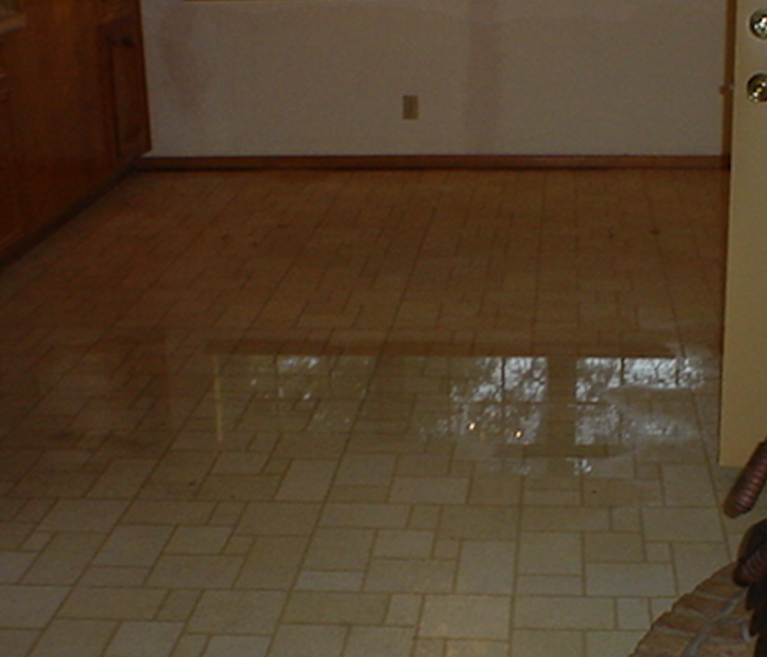 Kitchen tile with pool of water after a leak.