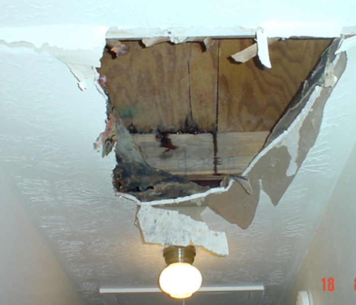Hole in a ceiling due to water damage.